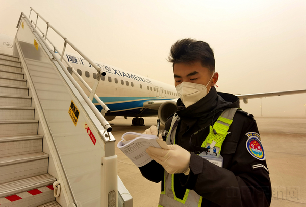 图:飞机监护员在沙尘中恪守岗亭.jpg