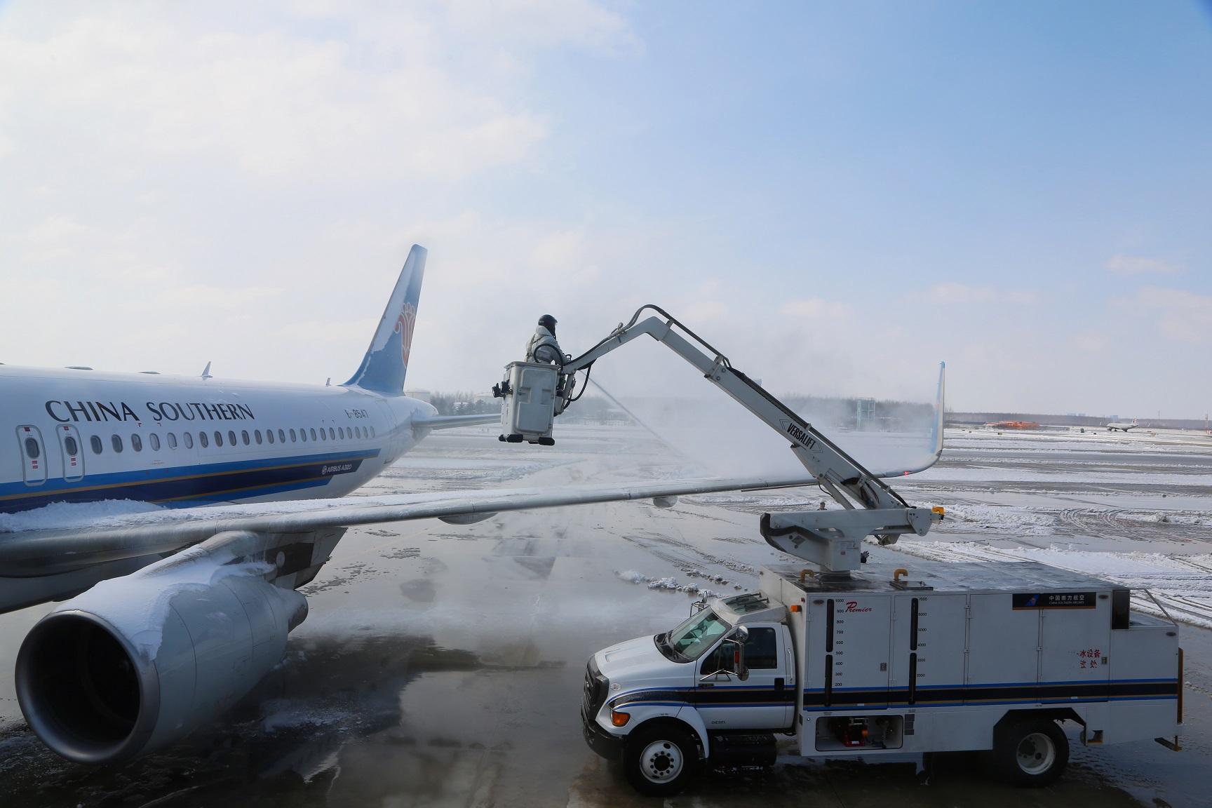 一名飞机除冰员 远处,机场除雪车也已经开始工作.